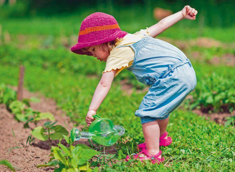 Meisje geeft de moestuin water