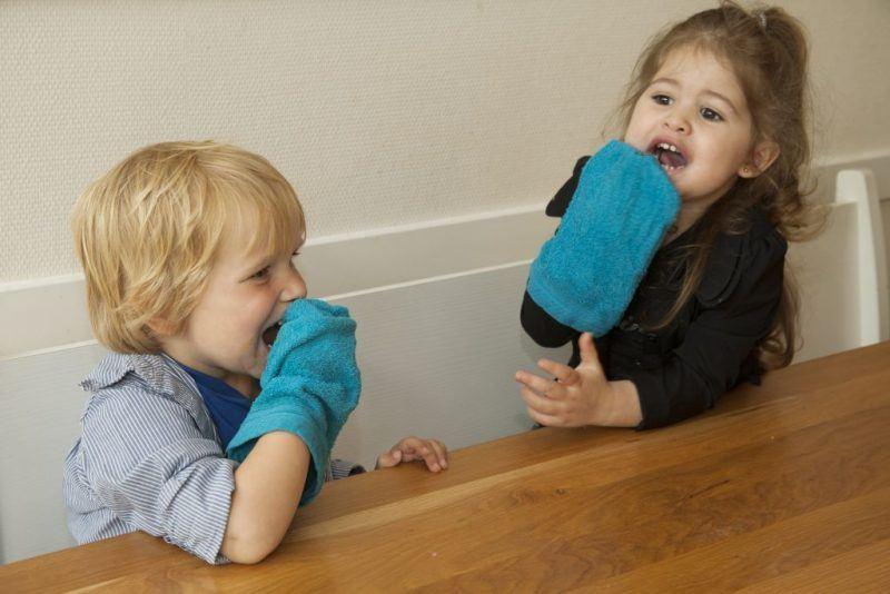 Kinderen maken gezicht schoon met washandje