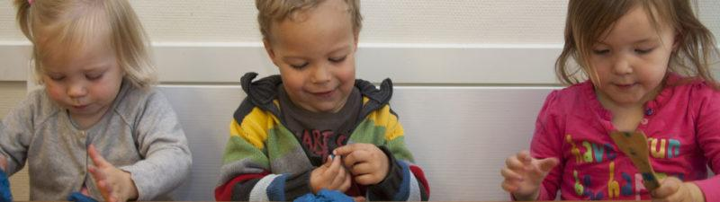 Drie kindjes spelen met klei